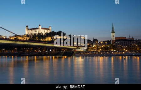 Night time view of the skyline of Bratislava from the shore of the Danube river.  View of the UFO bridge, the castle and the old town. - Stock Image