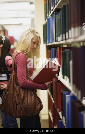A young woman examines a book in a library aisle - Stock Image