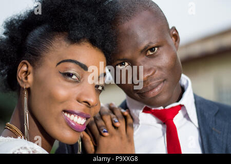 Close-up of young couple in love embracing smiling at the camera. - Stock Image