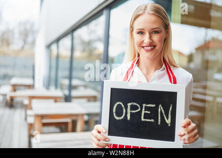 Young woman as a waitress holding an open chalk board in front of restaurant or bistro - Stock Image