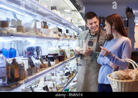 Male Sales Assistant Giving Advice To Female Customer In Delicatessen Shopping For Cheese - Stock Image