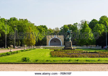 Poznan, Poland - April 29, 2018: Wilsona park with grass and tees and a sculpture. - Stock Image