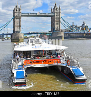 Tourists & commuters on high speed Thames Clipper catamaran public transport fast river bus with Tower Bridge iconic landmark beyond London England UK - Stock Image