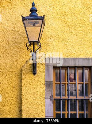 Old lamp on yellow lime washed wall in courtyard of Museum of Edinburgh, Royal Mile, Edinburgh, Scotland, UK - Stock Image