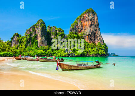 Boats at the beauty beach with limestone cliff and crystal clear water in Thailand - Stock Image