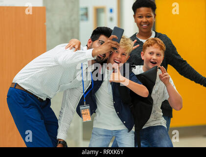 Junior high boy students and male teacher taking selfie with smart phone - Stock Image