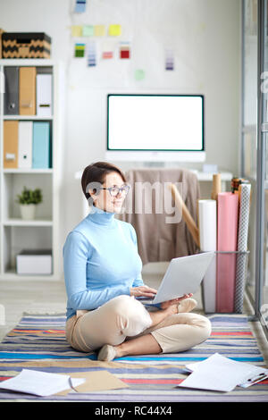Cross-legged office manager or analyst with laptop sitting on the floor and looking through websites in the net - Stock Image