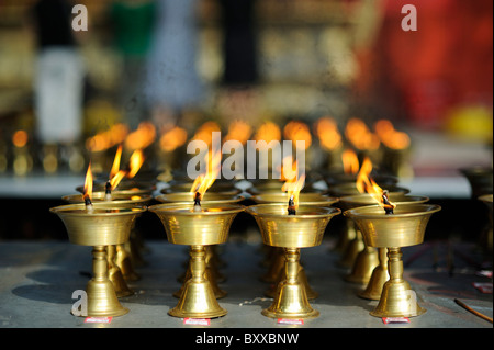 Butter lamps, buddhist temple, Leshan, China. - Stock Image