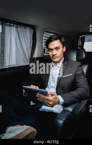 busy young executive using tablet while in the car on his way to the office - Stock Image