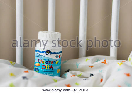 Poznan, Poland - November 8, 2018: Nordic Naturals Children's DHA cod liver oil in a plastic container on a baby bed. - Stock Image