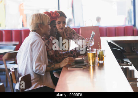 Young women friends looking at map, drinking cocktails in bar - Stock Image