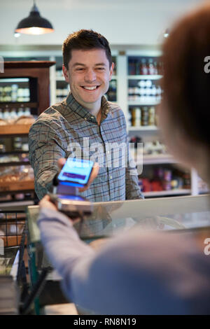 Male Customer Making Contactless Payment For Shopping Using Mobile Phone In Delicatessen - Stock Image