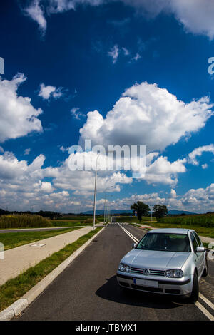 Front of a silver Volkswagen Golf IV parked on the street with beautiful blue cloudy sky in the background. - Stock Image