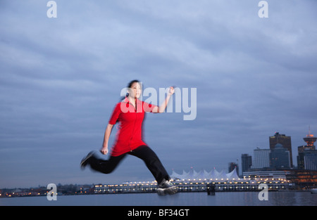 A young Asian woman leaps as she jogs along the Stanley Park seawall with Canada Place beyond, Vancouver, BC, Canada - Stock Image