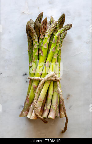 Bundle of fresh green asparagus on white marble board with copy space - Stock Image