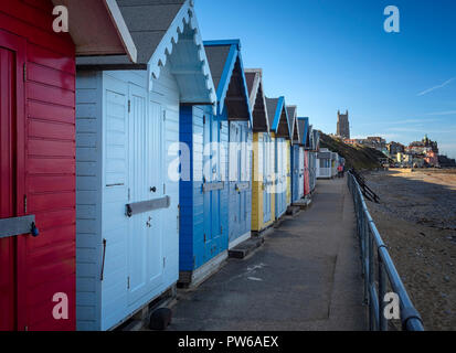 Colourful beach huts along the sandy shore at Cromer, north Norfolk, England, UK - Stock Image