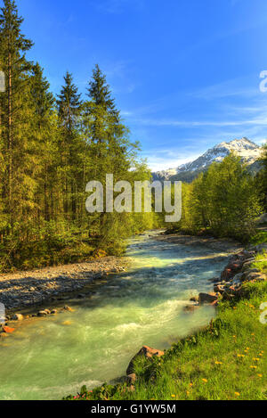 Bon Nant river flowing down from the mountains into Notre Dame de le Gorge in the French Alps - Stock Image