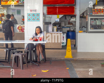 Asian woman sitting down eating breakfast al fresco at a restaurant in Singapore - Stock Image