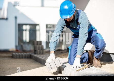 Builder in uniform laying paving tiles on the construction site with white houses on the background - Stock Image