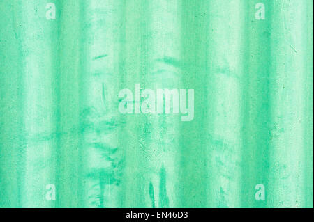 Close up of part of a sheet of green corrugated metal as a background image - Stock Image