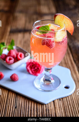 Refreshing raspberry peach mimosa drink on a wooden background - Stock Image