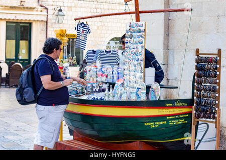 A buyer inspects a souvonir stall in Dubrovnik - Stock Image