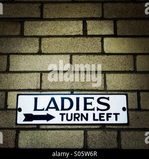 Ladies bathroom sign with wrong backward arrow. - Stock Image