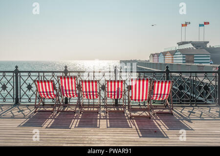 Deckchairs on Hastings Pier, East Sussex, UK - Stock Image