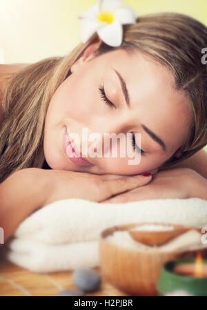 Closeup portrait of a peaceful woman with closed eyes lying down on a massage table in the spa salon, luxury healthy - Stock Image