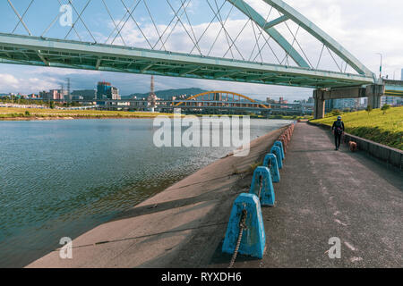 A woman walks her dog  under the bridges of Taipei along Keelung River in the Taipei River Park. - Stock Image