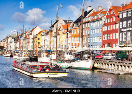 23 September 2018: Copenhagen, Denmark - Canal boat full of tourists sightseeing along the canal in the Copenhagen district of Nyhavn, with its colour - Stock Image