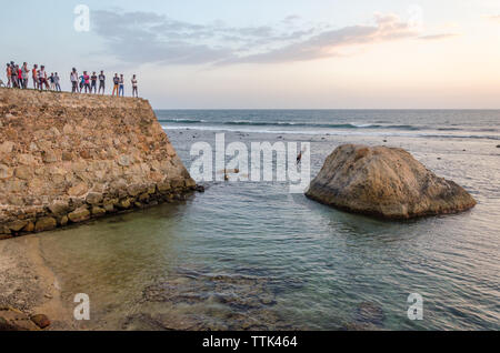 Boys jumping from Galle Fort into the shallow water of Galle Baty, Galle, Sri Lanka - Stock Image