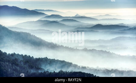Foggy landscape on the hills in a winter cold morning seen from the mountains near the city of Varese - Stock Image