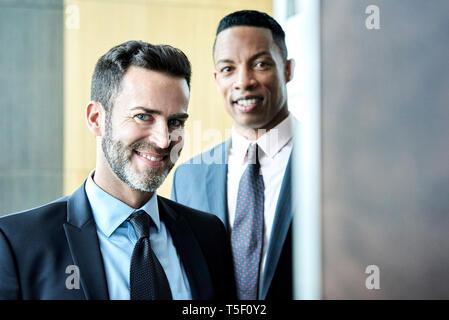 Smiling businessmen standing in hotel lobby - Stock Image