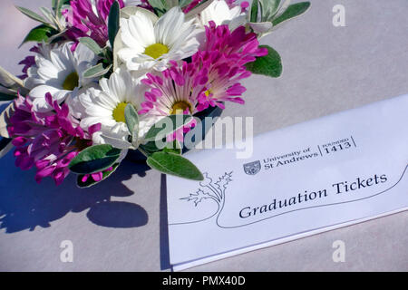 University of St Andrew's Graduation tickets on a table beside a flower decoration - Stock Image