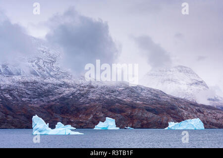 Greenland. Northeast Greenland National Park. Kong Oscar Fjord. Icebergs and dark, low clouds. - Stock Image
