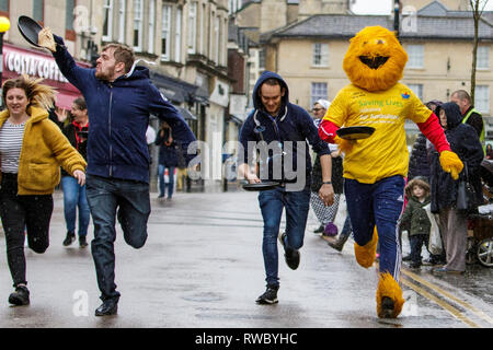 Chippenham, Wiltshire, UK. 5th March, 2019. Heavy rain this afternoon failed to dampen the spirits of local people taking part in the annual pancake race on Chippenham high street.  Credit: Lynchpics/Alamy Live News - Stock Image