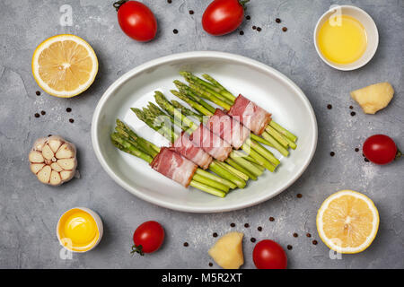 fresh green asparagus with bacon  in white bowl for baking on a gray background. view from above - Stock Image