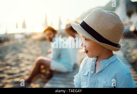 A small toddler boy with a hat standing on beach on summer holiday. Copy space. - Stock Image