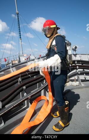 SOUTH CHINA SEA (March 15, 2019) Mineman Seaman Logan Hardy, from Millbrook, Alabama, prepares a firehose during a general quarters drill aboard the Avenger-class mine countermeasures ship USS Chief (MCM 14). Chief, part of Mine Countermeasure Squadron 7, is operating in the Indo-Pacific region to enhance interoperability with partners and serve as a ready-response platform for contingency operations. - Stock Image