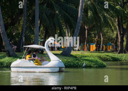 Tourists in swan pedal boat in Bangkok Lumpini park, Thailand - Stock Image