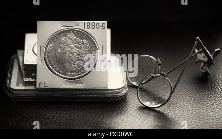 Coin Collector Desk with stack of coins featuring a beautiful mint state Morgan Dollar and magnifier glass in black and white - Stock Image