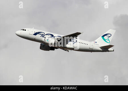 Adria Airways Airbus A319 in flight against a cloudy sky - Stock Image