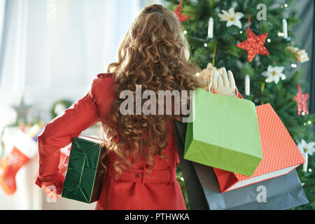 Seen from behind young woman in red trench coat with shopping bags and Christmas present box near Christmas tree - Stock Image