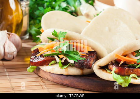 Gua bao, steamed buns with pork belly and vegetable. Asian cuisine - Stock Image