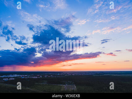 Cloudscape at sunset with beautiful cumulus clouds over fields and forests on a summer evening - Stock Image