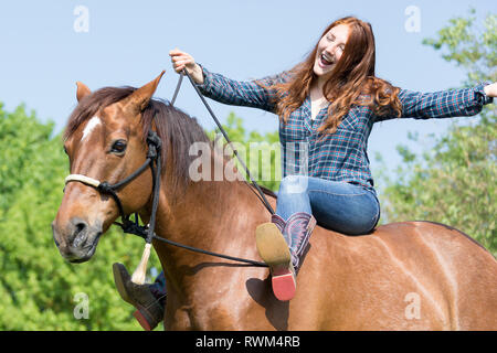 Missouri Fox Trotter. Red-haired young woman on chestnut gelding on a pasture, one boot on a rein. Switzerland - Stock Image