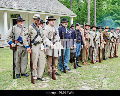 American Civil War reenactment soldiers in Confederate and Union uniforms stand in formation at battle recreation in Marbury Alabama USA. - Stock Image