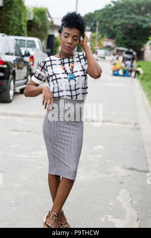 Young African woman model posing in the street and behind parked cars - Stock Image