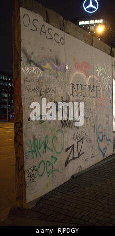 A photograph of some of the graffiti art on a panel of the Berlin Wall - Stock Image